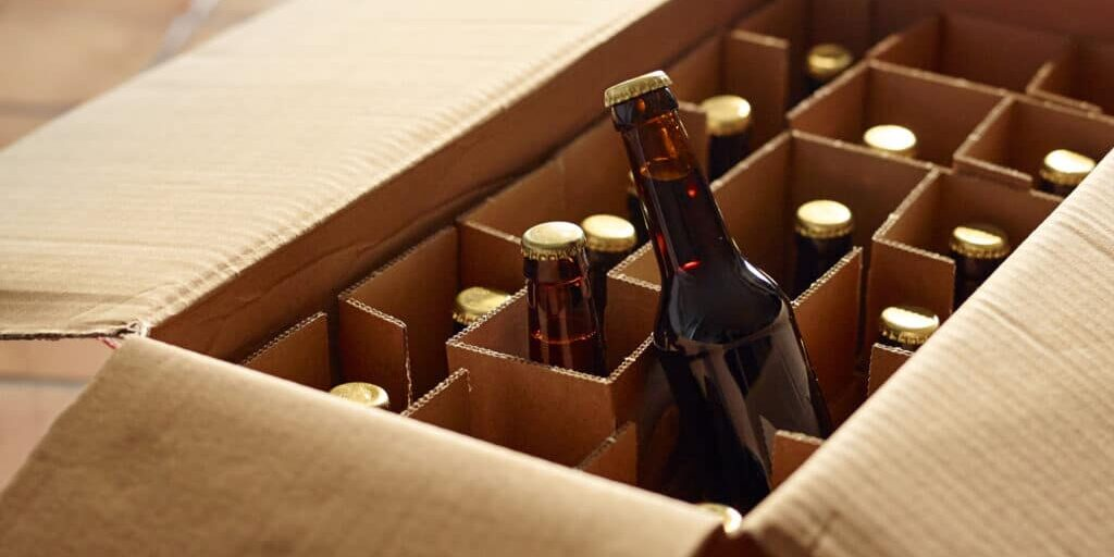 Unpacking a package of beer bottles from different breweries. Craft Beer from foreign countries or national micro breweries are hardly available in most regular stores. Online shops offer Craft beer or a selection of special beer and deliver it.